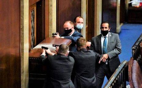 國會警察在國會大廈內拔槍保護國會議員及工作人員進入最近的辦公室避難